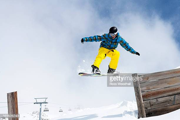 Snowboarder jumping off wooden fence