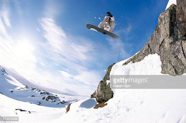 A snowboarder jumping out from a cliff.