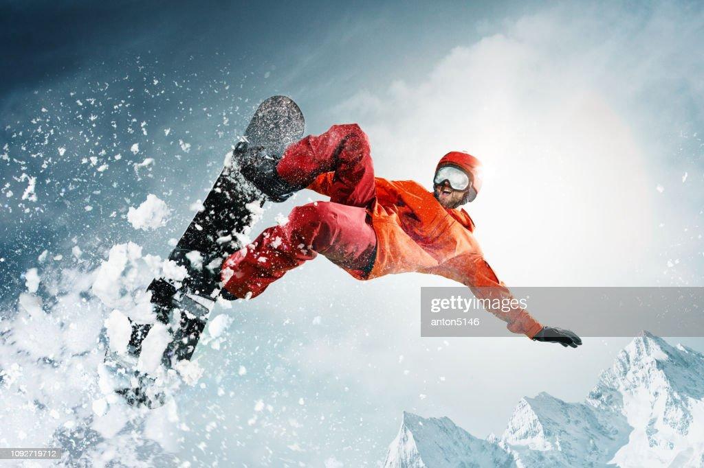Snowboarder salta a través del aire con el cielo azul de fondo : Foto de stock