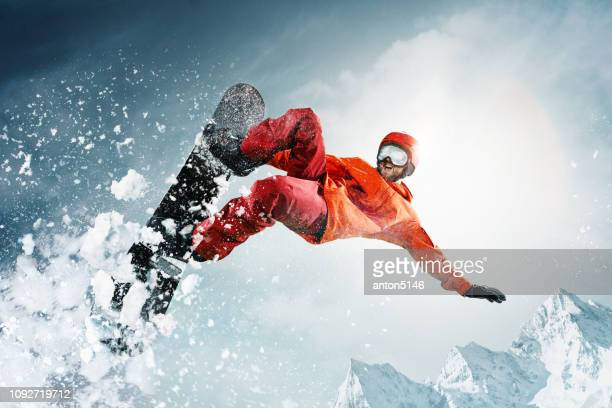 snowboarder jumping through air with deep blue sky in background - boarding stock pictures, royalty-free photos & images