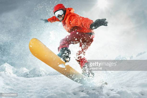 snowboarder jumping through air with deep blue sky in background - skiing stock pictures, royalty-free photos & images
