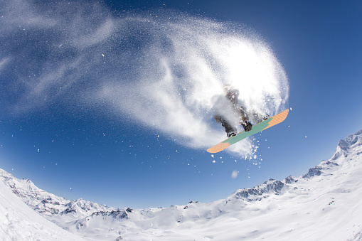 A Snowboarder jumps across a Mountain Range and Grabs his Snowboard. - gettyimageskorea