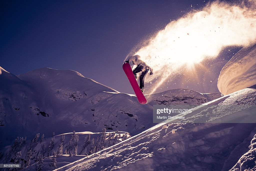 dynamic snowboard jump with flying snow and sun reflections
