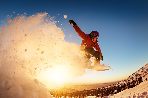 Snowboarder jumps sunset with snow dust 1029283208