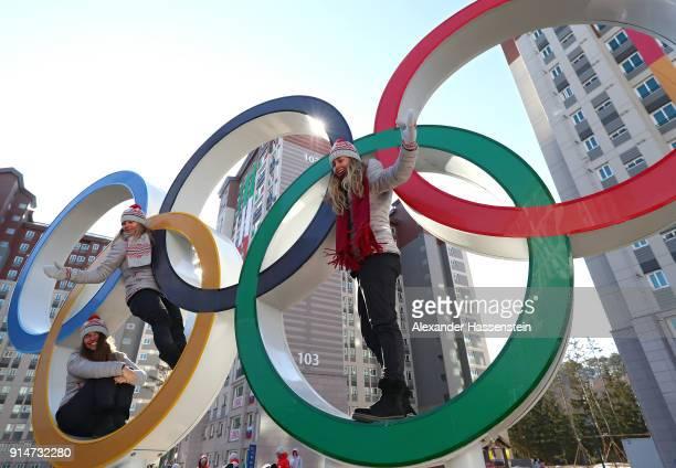 Snowboarder Klaudia Medlova and ski coaches Kjersti Ostgaard Buaas and Chanelle Sladics of Team Slovakia pose on the Olympic Rings in the Athletes'...