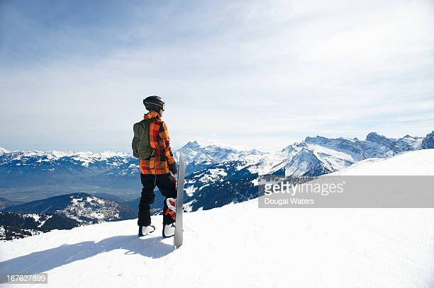 Snowboarder looking across mountain range.