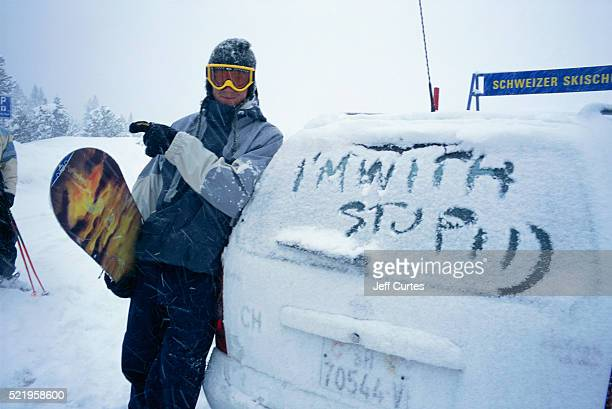 Snowboarder Near Writing of I'm with Stupid on SUV Window