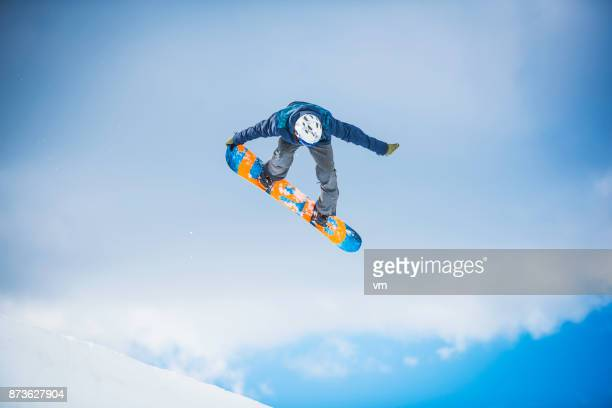 snowboarder performing a tail grab - boarding stock pictures, royalty-free photos & images