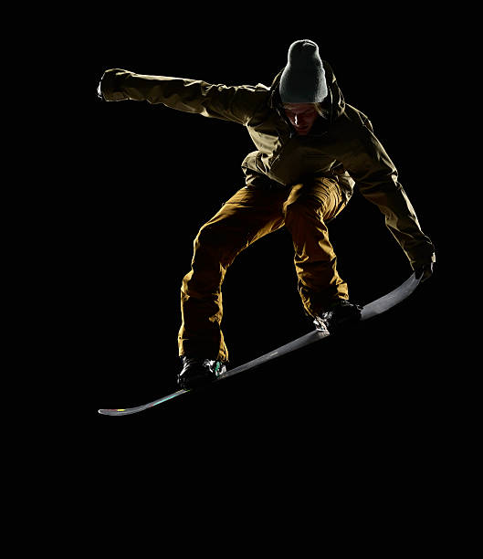 Snowboarder pulling front nose grab mid air