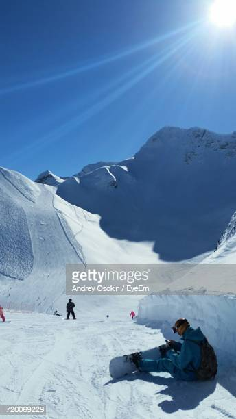 Snowboarder Sitting On Snow Against Sky