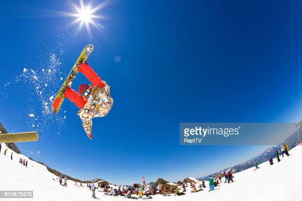 A Snowboarder somersaulting of a Log in a Snow park.