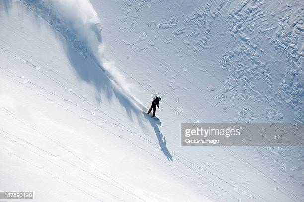 Snowboarder speeding down hill in powder snow flowing behind