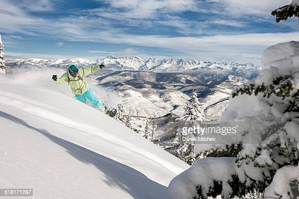 snowboarder taking powder turn in deep snow. - beaver creek colorado stock pictures, royalty-free photos & images