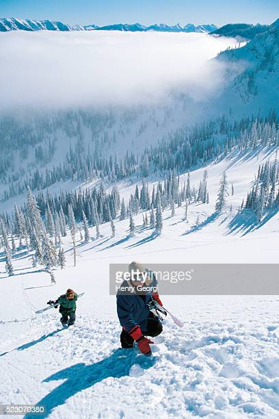 snowboarders carrying snowboards up mountain - ski wear stock pictures, royalty-free photos & images