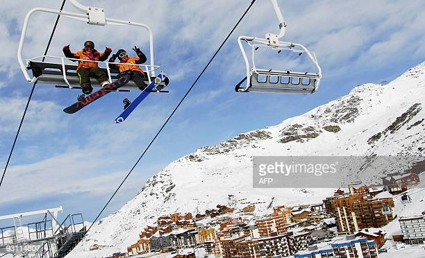 Snowboarders gesture from a chair lift in ValThorens on November 14 2009 as the ski resorts of Tignes and Val Thores opened part of their slopes at...