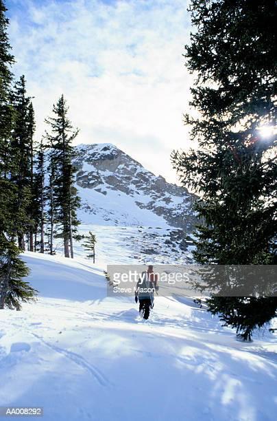 Snowboarders Hiking Through Snow Toward a Peak