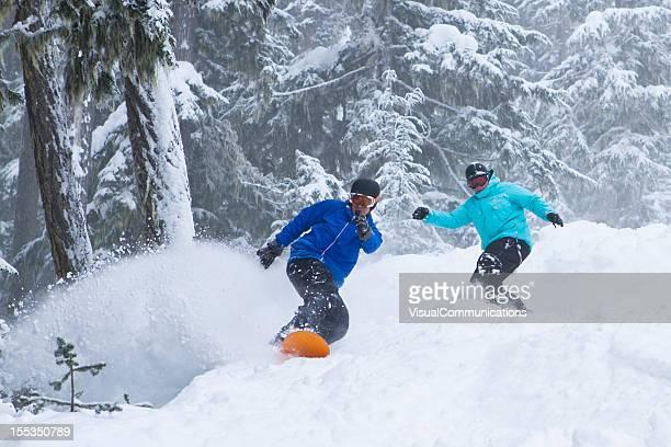 Snowboarders in deep powder.