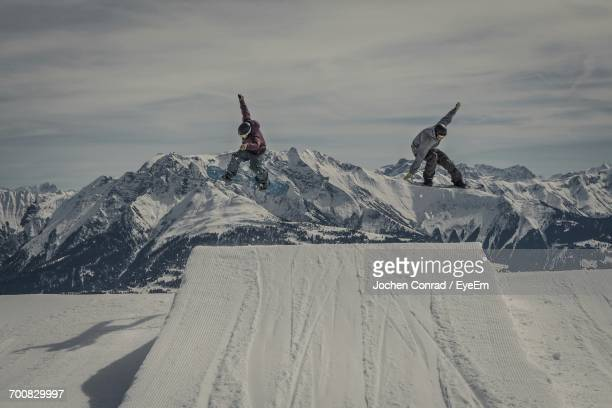 40029b9f1067 Snowboarders Jumping Over Snow Covered Ramp At Mountains Against Sky