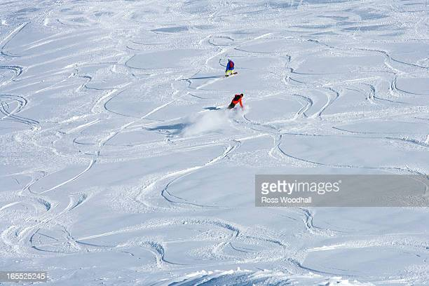 Snowboarders making tracks in snow