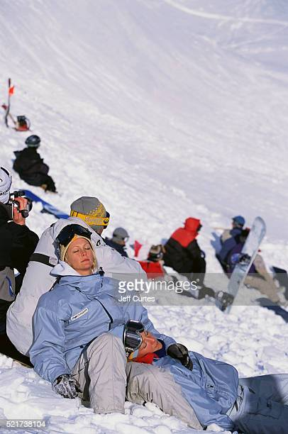 Snowboarders Relaxing on Mountain Slope
