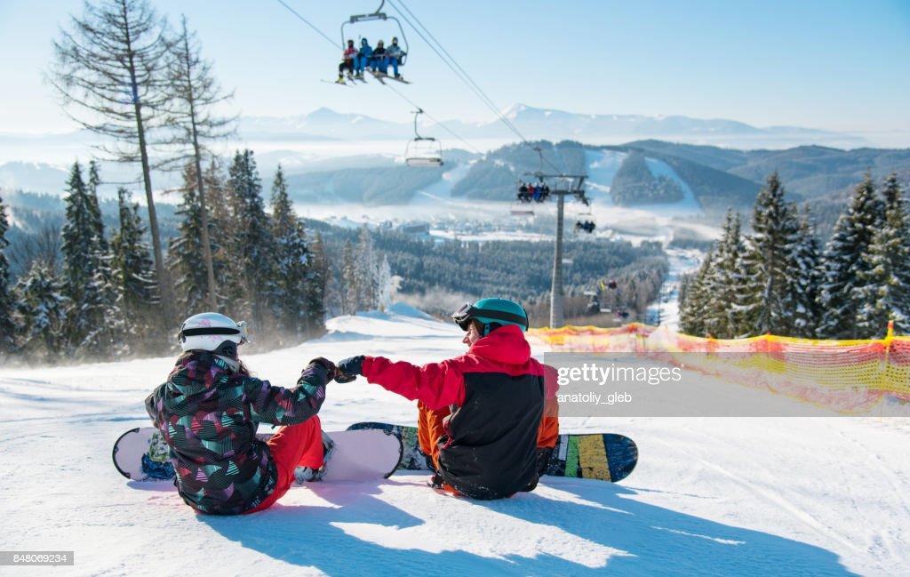 晴れた日にカルパティア山脈や森林の美しい風景と冬のリゾート地でスキー場のリフト下ゲレンデの上に休憩のスノーボーダー : ストックフォト
