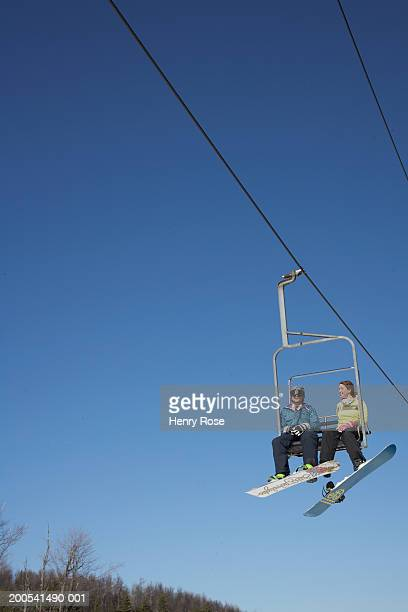 Snowboarders riding chair lift, low angle view