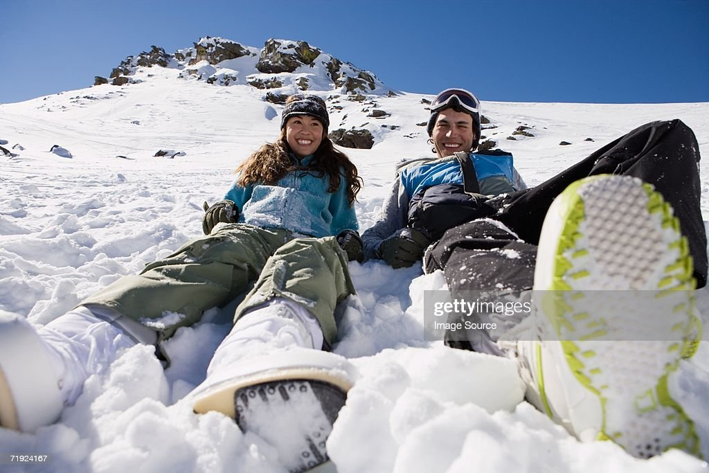 Snowboarders sitting in the snow : Stock Photo