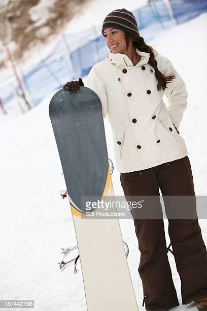 Snowboard donna in piedi sulla pista da sci