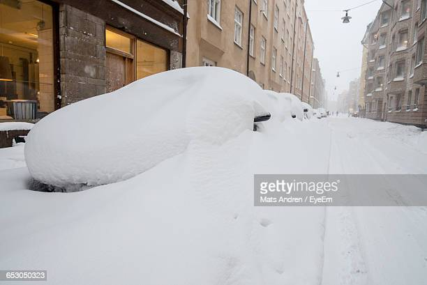 Snowcapped Cars By Street During Winter