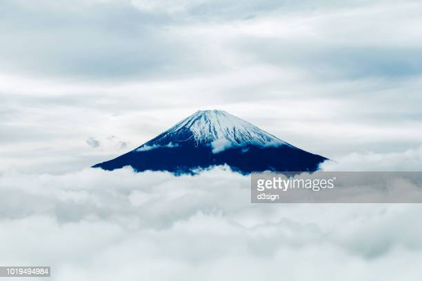 snowcapped mount. fuji (fujiyama) over a sea of clouds against sky - discovery stock pictures, royalty-free photos & images
