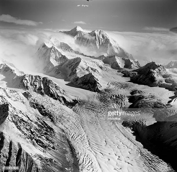 Snowcapped Mount Hayes sits in the background surrounded by a shear cloud layer beyond Susitna Glacier, Alaska Range. Septmeber 5, 1966.