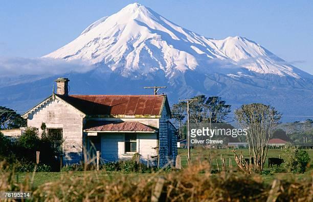 Snow-capped Mount Taranaki, with house in foreground, New Plymouth, North Island, Taranaki, New Zealand, Australasia
