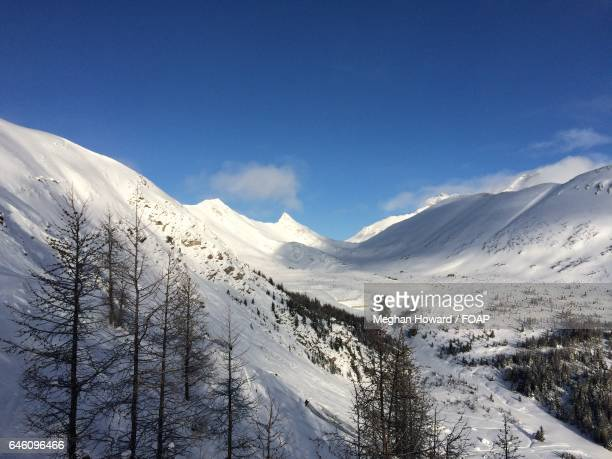 snowcapped mountain against sky - meghan stock photos and pictures