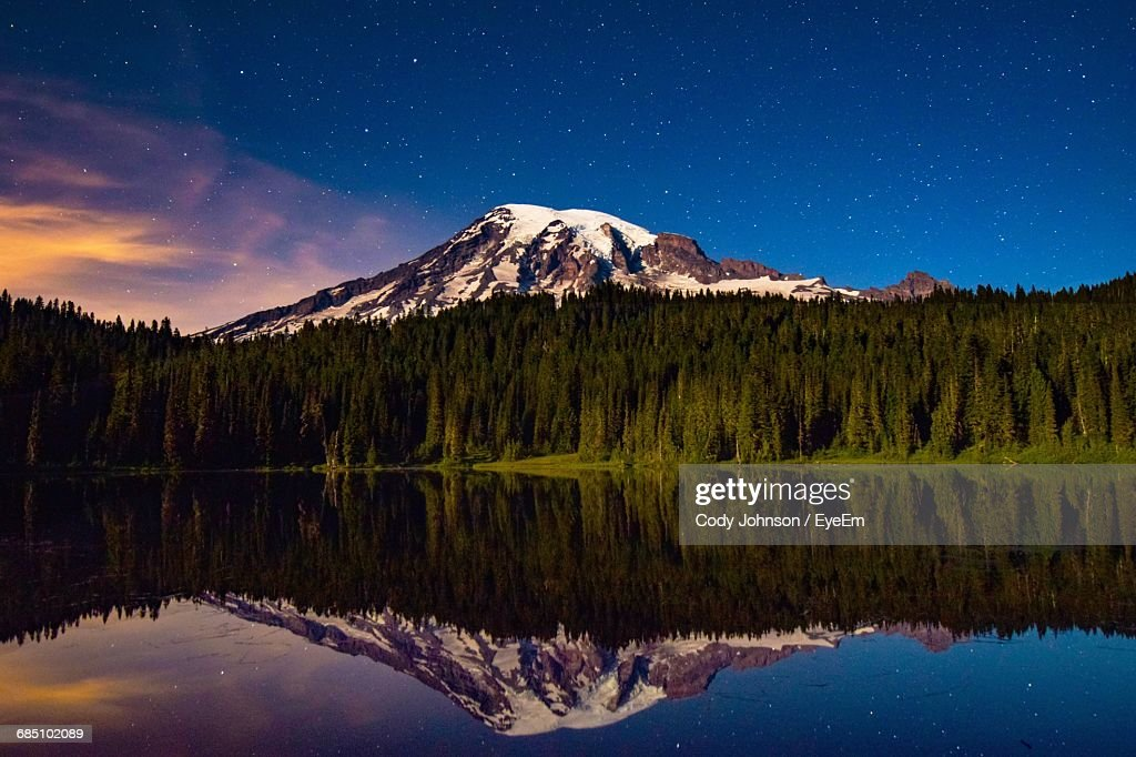 Snowcapped Mountain And Pine Trees Against Sky Reflecting In Lake During Sunrise At Mt Rainier National Park : Stock Photo