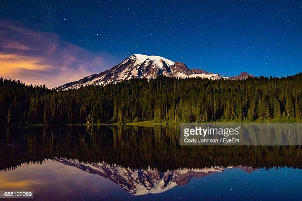 Snowcapped Mountain And Pine Trees Against Sky Reflecting In Lake During Sunrise At Mt Rainier National Park