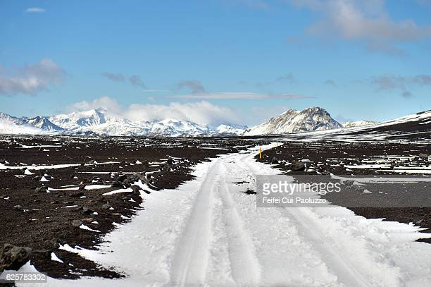 snowcapped mountain and snow covered road at maelifellsandur in highlands of iceland - altopiano foto e immagini stock