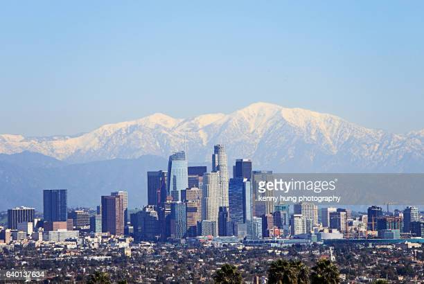 snowcapped mountain as background of downtown los angeles - los angeles skyline stock pictures, royalty-free photos & images