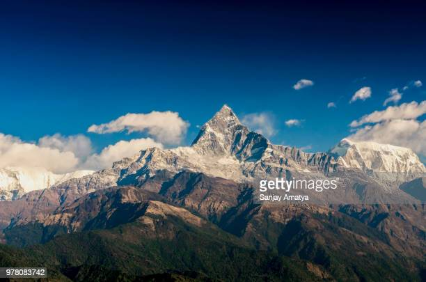Snow-capped mountain peak surrounded by clouds on sunny day, Sarangkot, Pokhara, Nepal