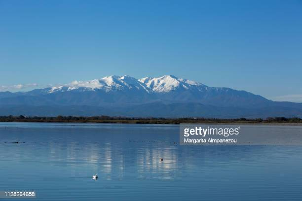 Snowcapped mountain reflected in the calm water of a lake