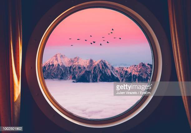 snowcapped mountains and clouds seen through circle shaped window - circle stock pictures, royalty-free photos & images