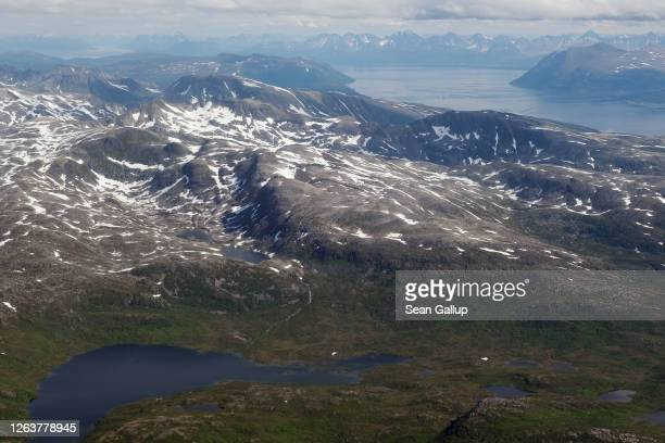 Snow-capped mountains and mountain lakes lie near a fjord as seen from a passenger plane window on July 28, 2020 near Tromso, Norway. Tromso is the...