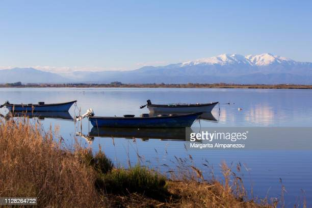 Snowcapped mountains, calm lake water, fishing boats and reflections