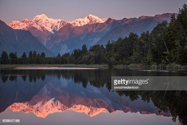 snowcapped mountains reflected in tranquil lake - mirror lake stock pictures, royalty-free photos & images