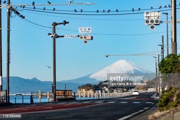 snow-capped mt. fuji and coast road in kanagawa prefecture of japan - 静岡県 ストックフォトと画像