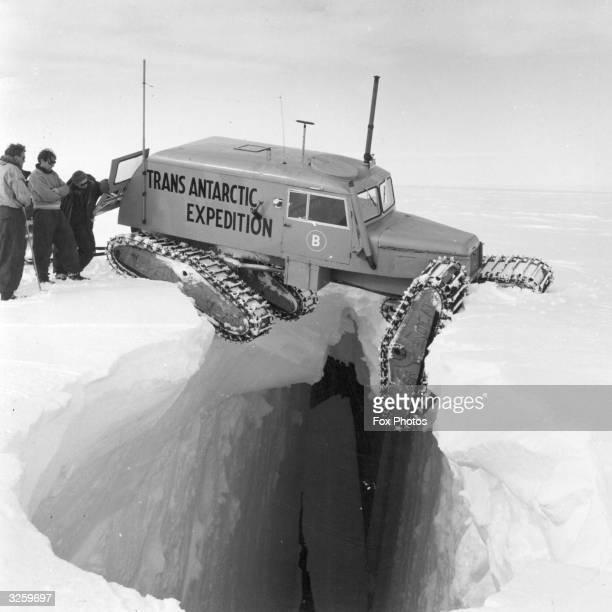 A snowcat balanced precariously over a crevice during a TransAntarctic Expedition