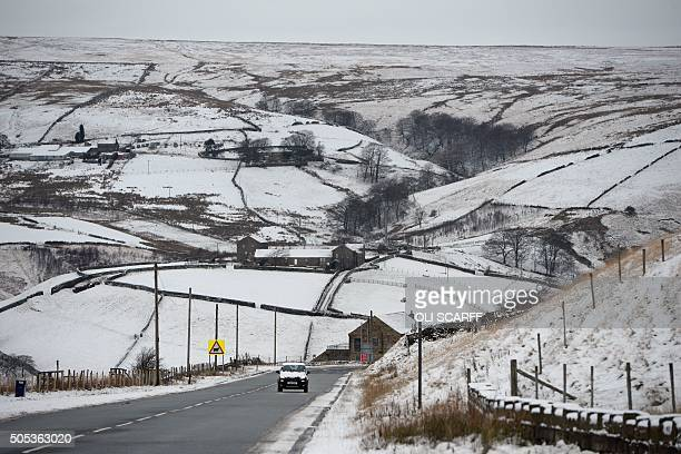 A snowcovered car drives past snowcovered fields near the village of Marsden near Huddersfield northern England on January 17 2016 AFP PHOTO / OLI...