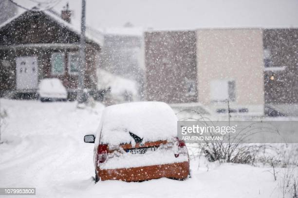 A snowcovered car is seen during heavy snow falls over Pristina on January 10 2019