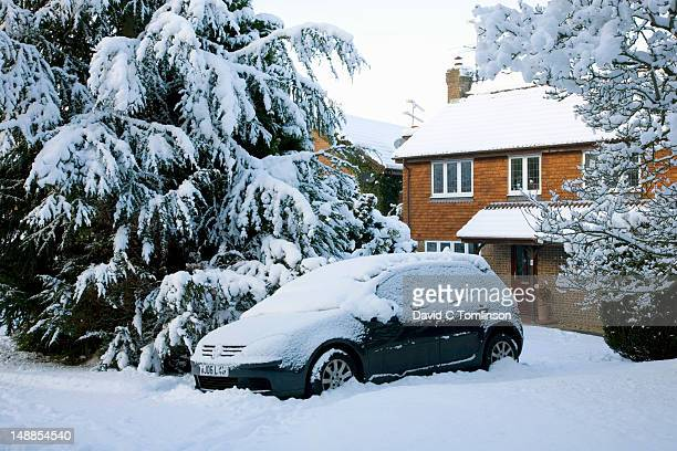 Snow-covered car parked in front of modern house.
