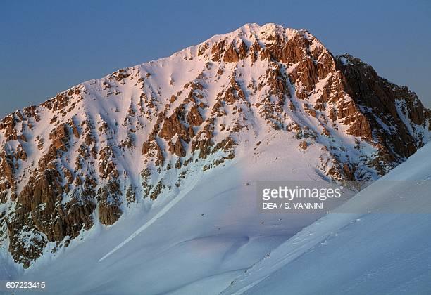 Snow-covered Corno Grande mountain at sunset, seen from the Duca degli Abruzzi mountain hut, Campo Imperatore, Gran Sasso and Monti della Laga...