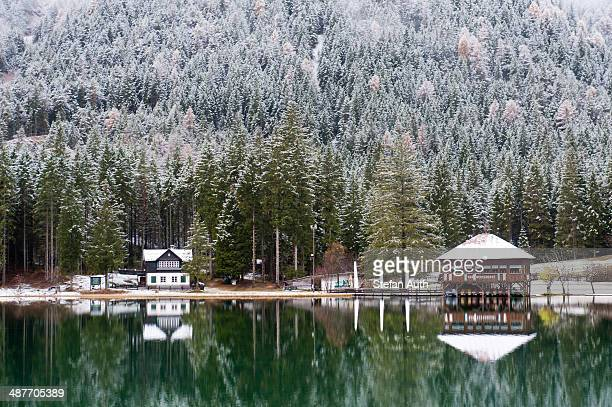 snow-covered forest and houses reflected in lake toblach, lago di dobbiaco, toblach, val pusteria, alto adige, trentino-alto adige, italy - toblach stock photos and pictures